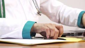 Καλλιεργημένος κοντά επάνω ενός θηλυκού γιατρού που χρησιμοποιεί τις έξυπνες σημειώσεις τηλεφωνικού γραψίματος απόθεμα βίντεο