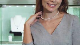 Καλλιεργημένος κοντά επάνω μιας ευτυχούς γυναίκας που χαμογελά φορώντας το περιδέραιο μαργαριταριών απόθεμα βίντεο