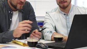 Καλλιεργημένος πυροβολισμός δύο επιχειρησιακών συναδέλφων αρσενικών που έχουν τον καφέ που συζητά την εργασία απόθεμα βίντεο