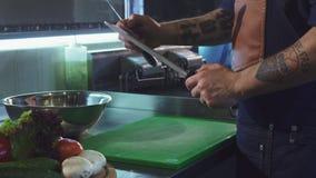 Καλλιεργημένος πυροβολισμός ενός επαγγελματικού αρχιμάγειρα που ακονίζει το μαχαίρι του απόθεμα βίντεο