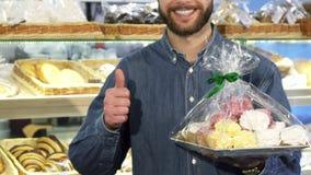 Καλλιεργημένος πυροβολισμός ενός ευτυχούς γενειοφόρου ατόμου που παρουσιάζει αντίχειρες στο αρτοποιείο στοκ εικόνες