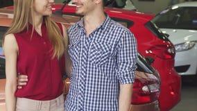 Καλλιεργημένος πυροβολισμός ενός ζεύγους που χαμογελά παρουσιάζοντας κλειδιά αυτοκινήτων στον αντιπρόσωπο απόθεμα βίντεο