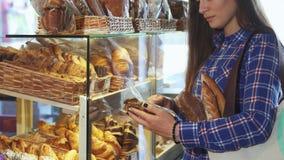 Καλλιεργημένος πυροβολισμός ενός θηλυκού πελάτη που εξετάζει το πακέτο των μπισκότων στο αρτοποιείο φιλμ μικρού μήκους