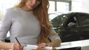 Καλλιεργημένος πυροβολισμός ενός θηλυκού πελάτη που υπογράφει τα έγγραφα στην αίθουσα εκθέσεως αντιπροσώπων φιλμ μικρού μήκους