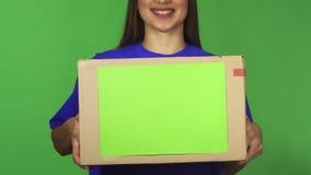 Καλλιεργημένος πυροβολισμός ενός κιβωτίου εκμετάλλευσης χαμόγελου γυναικών παράδοσης carboard με το copyspace απόθεμα βίντεο