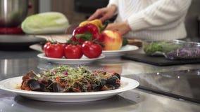 Καλλιεργημένος πυροβολισμός ενός μαγειρέματος γυναικών στην κουζίνα απόθεμα βίντεο