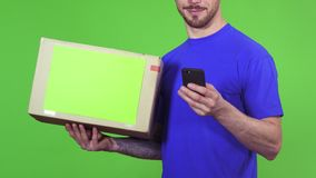 Καλλιεργημένος πυροβολισμός ενός deliveryman με μια συσκευασία που ο πελάτης του που χρησιμοποιεί το έξυπνο τηλέφωνο φιλμ μικρού μήκους
