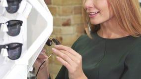 Καλλιεργημένος πυροβολισμός μιας γυναίκας που χαμογελά εξετάζοντας τα γυαλιά ηλίου στο κατάστημα φιλμ μικρού μήκους