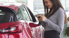 Καλλιεργημένος πυροβολισμός μιας γυναίκας που χρησιμοποιεί το έξυπνο τηλέφωνό της που στέκεται κοντά στο αυτοκίνητό της απόθεμα βίντεο