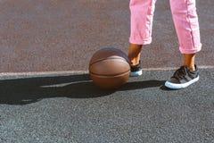 Καλλιεργημένος πυροβολισμός μιας σφαίρας καλαθοσφαίρισης που τοποθετείται στα πόδια της γυναίκας στοκ φωτογραφίες