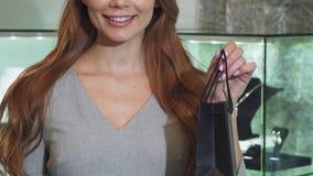 Καλλιεργημένος πυροβολισμός μιας τσάντας αγορών εκμετάλλευσης χαμόγελου γυναικών απόθεμα βίντεο