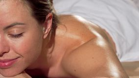 Καλλιεργημένος πυροβολισμός μιας όμορφης γυναίκας που κλείνει τα μάτια της, που περιμένει τη σύνοδο μασάζ απόθεμα βίντεο