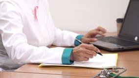 Καλλιεργημένος πυροβολισμός σημειώσεων ενός των θηλυκών γιατρών γραψίματος που χρησιμοποιούν το lap-top της στην εργασία φιλμ μικρού μήκους