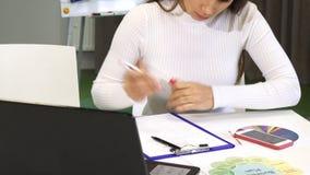 Καλλιεργημένος πυροβολισμός σημειώσεων ενός των νέων επιχειρησιακών γυναικών γραψίματος στο γραφείο φιλμ μικρού μήκους