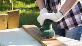 Καλλιεργημένος πυροβολισμός της γυναίκας τεχνών που γυαλίζει την ξύλινη σανίδα με ηλεκτρικό sander φιλμ μικρού μήκους