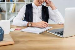 Καλλιεργημένος πυροβολισμός της συνεδρίασης επιχειρηματιών στο γραφείο, μιλώντας στην κάσκα και το γράψιμο στοκ εικόνες