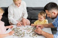 καλλιεργημένος πυροβολισμός του ευτυχούς οικογενειακού παιχνιδιού με τα κομμάτια γρίφων στοκ φωτογραφίες