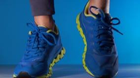 Καλλιεργημένος πυροβολισμός του νέου αθλητικού τύπου αφροαμερικάνων στο άλμα πάνινων παπουτσιών απόθεμα βίντεο