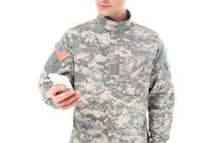καλλιεργημένος πυροβολισμός του στρατιώτη στη στρατιωτική στολή που χρησιμοποιεί το smartphone Στοκ Φωτογραφίες