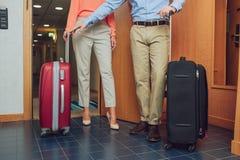 καλλιεργημένος πυροβολισμός του ώριμου ζεύγους με τις βαλίτσες που εισάγονται Στοκ Εικόνες