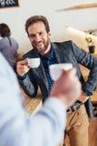 καλλιεργημένος πυροβολισμός των επιχειρηματιών που κρατούν τα φλιτζάνια του καφέ και το κοίταγμα στοκ φωτογραφία