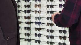 Καλλιεργημένος πυροβολισμός των χεριών ενός ατόμων τινάγματος με optometrist στο eyewear κατάστημα φιλμ μικρού μήκους