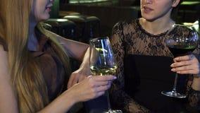 Καλλιεργημένος πυροβολισμός χαμόγελου δύο του νέου ευτυχούς γυναικών που μιλά πέρα από ένα ποτήρι του κρασιού στο φραγμό φιλμ μικρού μήκους