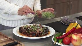 Καλλιεργημένος clsoe επάνω μιας γυναίκας που διακοσμεί το εύγευστο πιάτο με τα πράσινα που μαγειρεύει στο σπίτι απόθεμα βίντεο