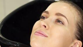Καλλιεργημένος sclose επάνω μιας γυναίκας που παίρνει την τρίχα της έπλυνε στο σαλόνι ομορφιάς απόθεμα βίντεο