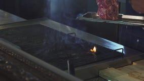 Καλλιεργημένο πυροβοληθε'ν φ ένας αρχιμάγειρας που ψήνει την μπριζόλα στην κουζίνα εστιατορίων στη σχάρα απόθεμα βίντεο