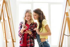 Καλλιτέχνες με το smartphone στο στούντιο ή το σχολείο τέχνης Στοκ Εικόνες