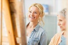 Καλλιτέχνες που συζητούν τη ζωγραφική easel στο σχολείο τέχνης Στοκ Φωτογραφίες
