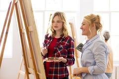 Καλλιτέχνες που συζητούν τη ζωγραφική easel στο σχολείο τέχνης Στοκ Φωτογραφία