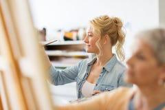 Καλλιτέχνης γυναικών με τη ζωγραφική βουρτσών στο σχολείο τέχνης Στοκ Φωτογραφίες