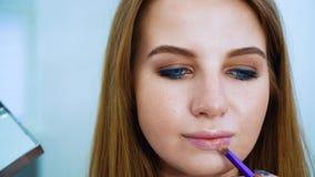 Καλλιτέχνης κινηματογραφήσεων σε πρώτο πλάνο makeup που εφαρμόζει τα καλλυντικά για το χαριτωμένο κορίτσι με τα μπλε μάτια και τη απόθεμα βίντεο