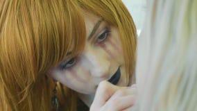 Καλλιτέχνης με αποκριές makeup που εφαρμόζουν αποκριές makeup στο πρότυπο πρόσωπο ` s απόθεμα βίντεο