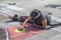 Καλλιτέχνης οδών που επισύρει την προσοχή στο πεζοδρόμιο με την κιμωλία Στοκ Εικόνες