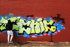 Καλλιτέχνης οδών που χρωματίζει τα ζωηρόχρωμα γκράφιτι στον κόκκινο τοίχο στοκ φωτογραφία με δικαίωμα ελεύθερης χρήσης