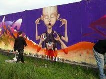 Καλλιτέχνης οδών που χρωματίζει τα ζωηρόχρωμα γκράφιτι στο γενικό τοίχο Στοκ Εικόνες