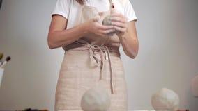 Καλλιτέχνης που εργάζεται με τα μεγάλα κομμάτια αργίλου σε ένα εργαστήριο απόθεμα βίντεο