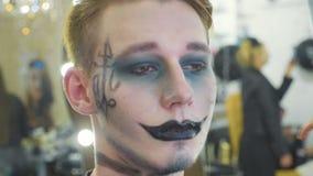 Καλλιτέχνης που εφαρμόζει αποκριές makeup στο αρσενικό πρότυπο πρόσωπο ` s απόθεμα βίντεο