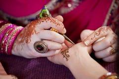 Καλλιτέχνης που εφαρμόζει Henna στην παλάμη ενός χεριού Womanâs Στοκ Φωτογραφίες