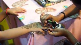 Καλλιτέχνης που εφαρμόζει henna τη δερματοστιξία σε ετοιμότητα παιδιών απόθεμα βίντεο