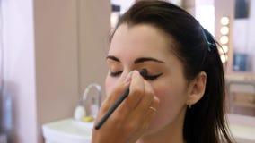 Καλλιτέχνης σύνθεσης χεριών που εφαρμόζεται makeup στο πρόσωπο μιας νέας γυναίκας Κορίτσι που κάνει το μάτι makeup σε ένα επαγγελ απόθεμα βίντεο