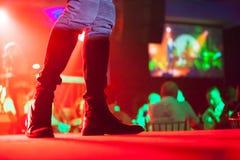 Καλλιτέχνης την ώρα της παράστασης στο στάδιο που φορά τις όμορφες μπότες της ενώ ο φιλοξενούμενος έχει το γεύμα Στοκ Εικόνες