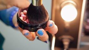 Καλλιτέχνης χεριών makeup που χρησιμοποιεί την καλλυντικά βούρτσα και το blusher για να ισχύσει στο πρόσωπο απόθεμα βίντεο