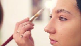 Καλλιτέχνης Makeup που επισύρει την προσοχή στο πρότυπο πρόσωπο ` s απόθεμα βίντεο