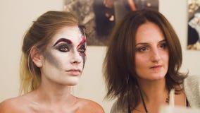 Καλλιτέχνης Makeup που επισύρει την προσοχή στο πρότυπο πρόσωπο ` s φιλμ μικρού μήκους