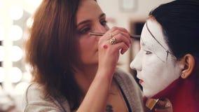 Καλλιτέχνης Makeup που επισύρει την προσοχή τη γραμμή στο πρότυπο πρόσωπο ` s φιλμ μικρού μήκους