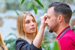 Καλλιτέχνης Makeup που ισχύει makeup στο πρότυπο πρίν πυροβολεί τη σειρά Στοκ Εικόνες